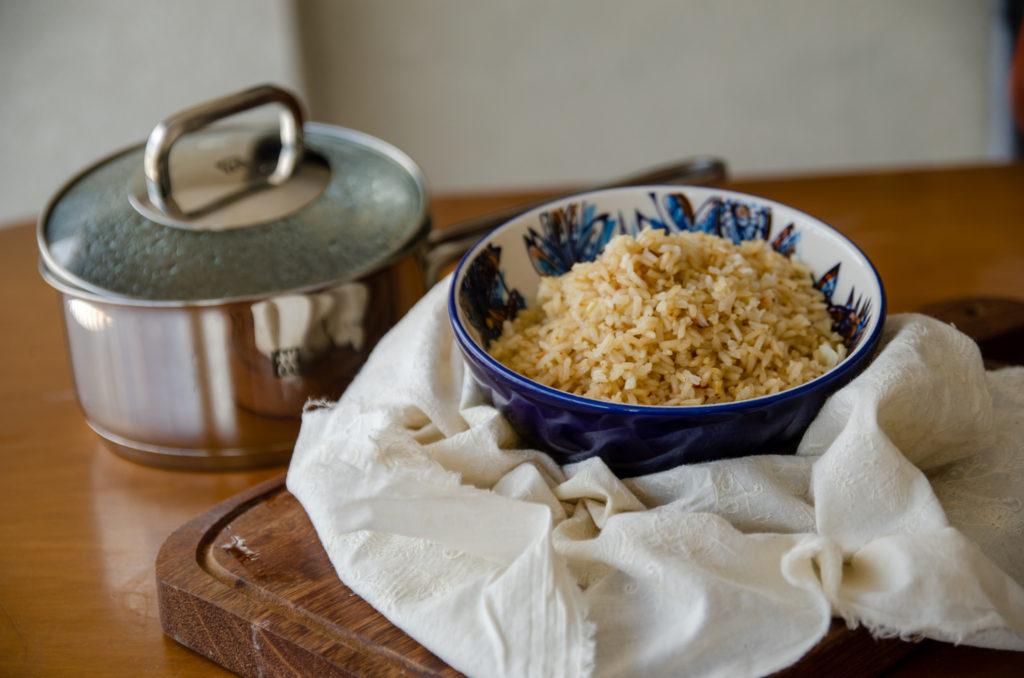 na foto: Panela atrás de uma tigela azul com arroz integral soltinho sobre um tecido bege e tábua de madeira
