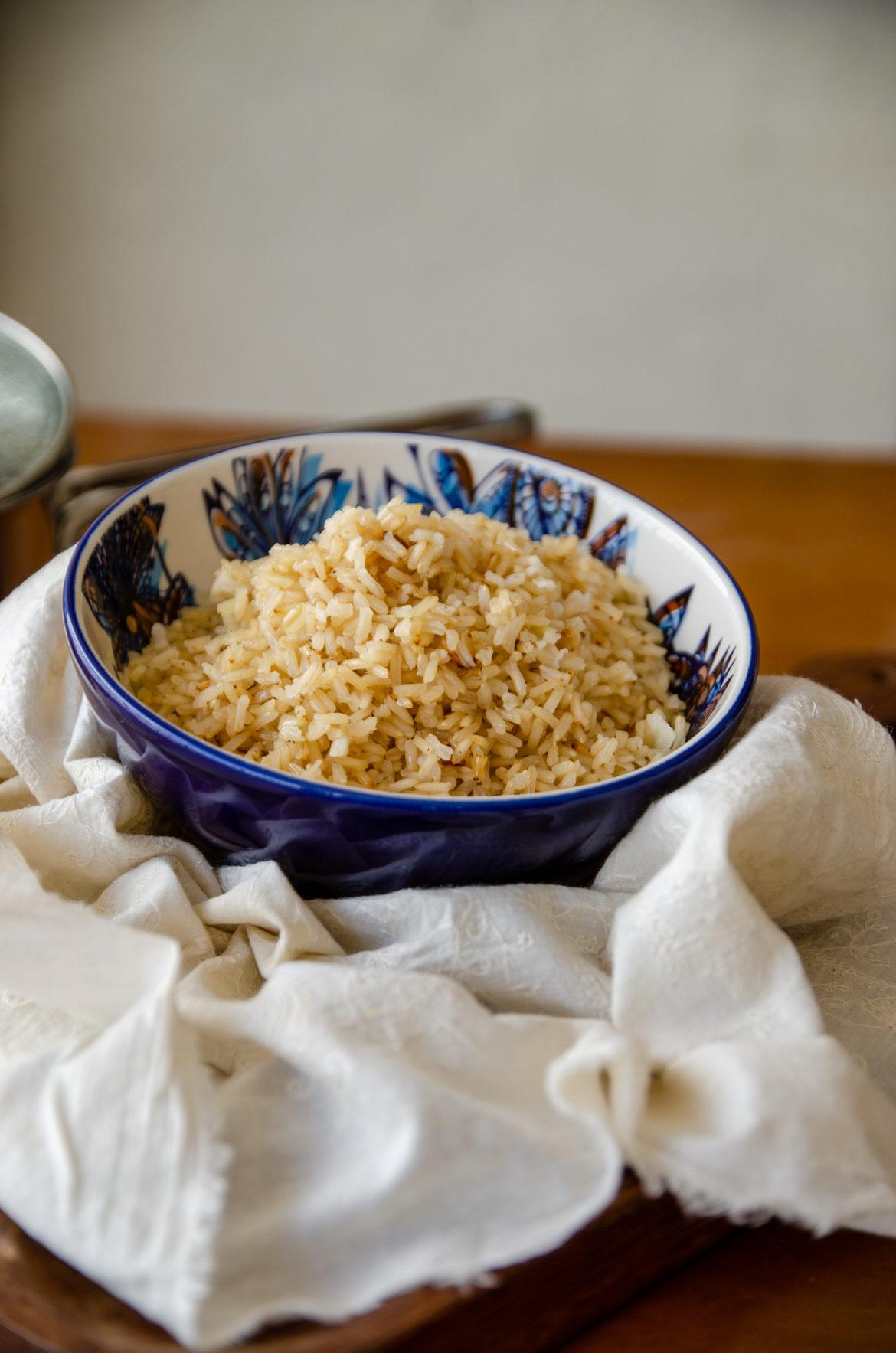 Tigela azul com arroz integral soltinho sobre um tecido bege e tabua de madeira escura