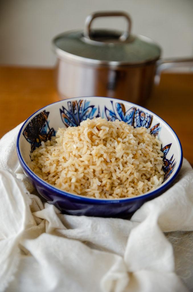 arroz integral soltinho em uma bacia azul sobre a mesa de madeira com panela desfocada atrás