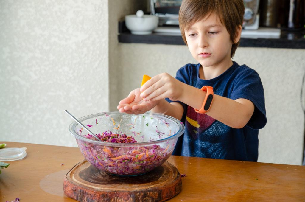 criança temperando os ingredientes da salada de repolho roxo com um limão