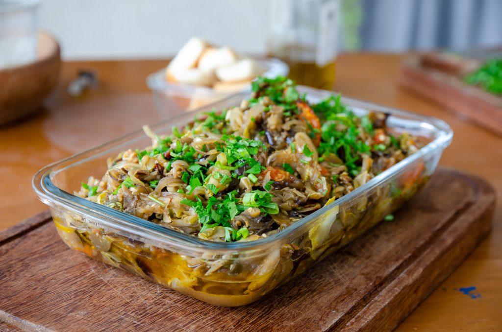 assadeira com a receita de abobrinha e berinjela de forno já assados, sobre uma tábua de madeira escura e muito cheiro verde em cima