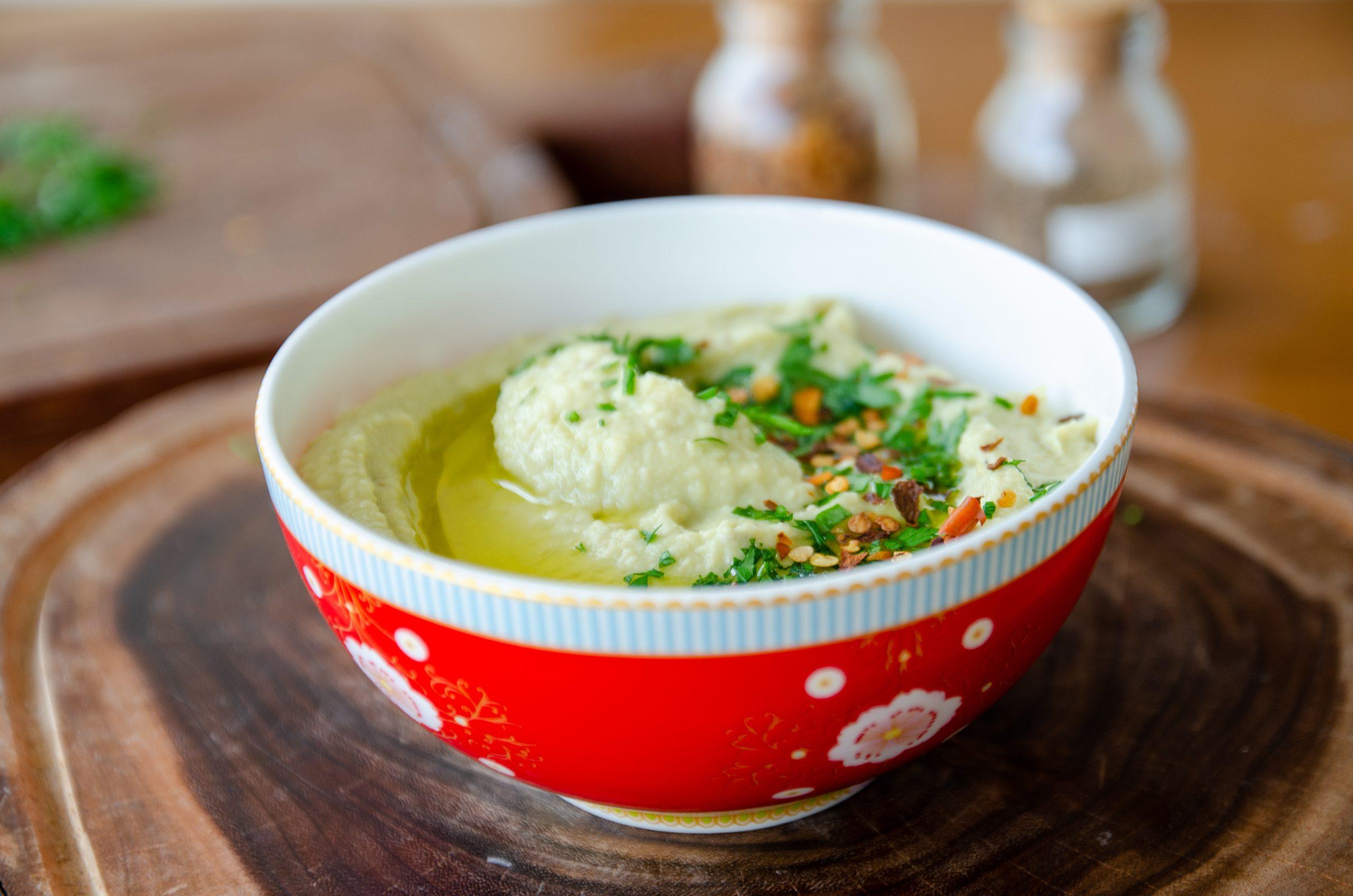 bowl vermelho sobre tábua de madeira com homus de grão de bico com abacate